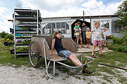 Abigail Schiebout, 8, sits in a cart chewing on the last bit of carrot while her sister Miriam, 9, sticks out her tongue at Millsap Farm on Tuesday, June 14, 2016. CSA members are required to work 12 hours on the farm.