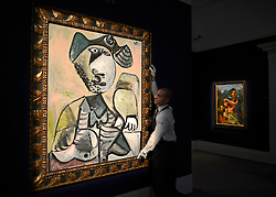 "© Licensed to London News Pictures. 14/06/2012. London, UK A gallery technician holds Pablo Picasso's ""Homme assis'  which is estimated to fetch 6-9MillionGBP. Photocall for Sotheby's June Impressionist and Modern Art Sale this June. Photo credit : Stephen Simpson/LNP"
