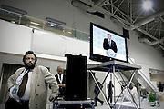ROMA. UN GIORNALISTA ASCOLTA IL DISCORSO DEL PRESIDENTE DEL CONSIGLIO SILVIO BERLUSCONI ALL'INTERNO DELLA SALA STAMPA ALLESTITA IN UNO DEI PADIGLIONI DELLA FIERA DI ROMA IN OCCASIONE DEL PRIMO CONGRESSO NAZIONALE DEL PARTITO DEL POPOLO DELLA LIBERTA'