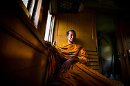 Monk reclines as a local train outside Bangkok transports its passengers in open air cars to their destination