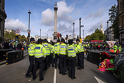 © Licensed to London News Pictures. 10/10/2019. London, UK. Police gather to move in on Extinction Rebellion activists on the roads around Trafalgar Square in Westminster, central London where they have been demonstrating for a fourth day running. The climate change group have blockaded the Westminster area, demanding that the government takes immediate and decisive action on climate change. Photo credit: Ben Cawthra/LNP
