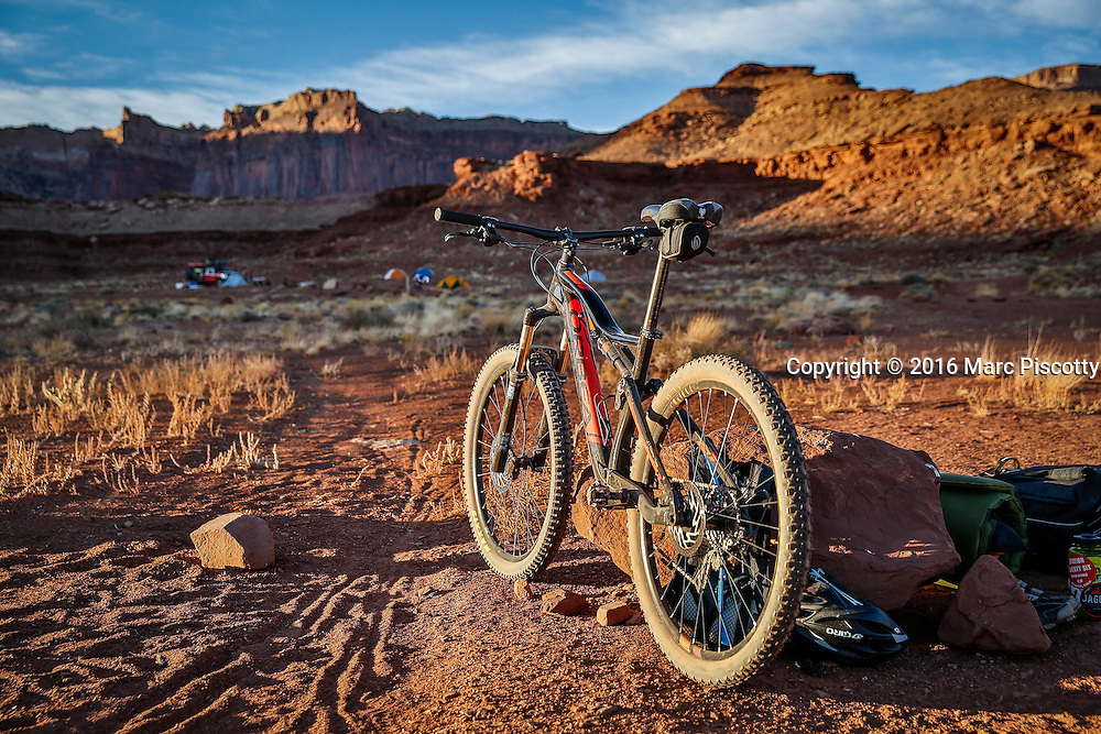 SHOT 10/16/16 5:56:58 PM - Tom Reynold's Orbea mountain bike parked for the evening at the Airport camping spot during the White Rim mountain biking trip in Canyonlands National Park just outside of Moab, Utah. The White Rim Road is a 71.2-mile-long unpaved four-wheel drive road that traverses the top of the White Rim Sandstone formation below the Island in the Sky mesa of Canyonlands National Park in southern Utah in the United States. The road was constructed in the 1950s by the Atomic Energy Commission to provide access for individual prospectors intent on mining uranium deposits for use in nuclear weapons production during the Cold War. Four-wheel drive vehicles and mountain bikes are the most common modes of transport though horseback riding and hiking are also permitted.<br /> (Photo by Marc Piscotty / &copy; 2016)