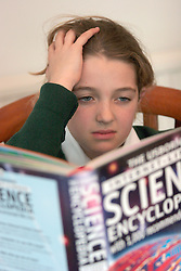 10 year old schoolgirl doing science homework looking worried of having difficulty UK