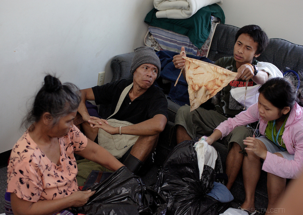 Ler Bweh, a 25-year-old Karen refugee from Burma and his wife Htee Shee Paw,17, look through donated clothes along with Ler Bweh's parents Mu Mu Po and Toe Toe Po shortly after arriving in the United States. This photo was taken on Oct. 4, 2007.  (Photo by Robert Falcetti)