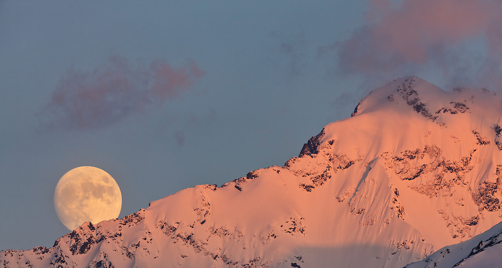 A nearly full moon rises behind Eagle Peak bathed in alpine glow minutes before sunset in mid-spring in the Chugach Mountains of Southcentral Alaska. Evening.