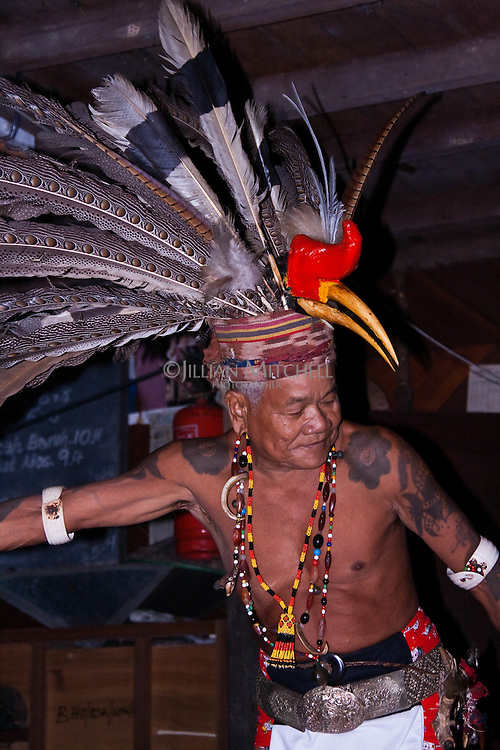 Chief Bansing is a well known tribal dancer.   Here he performs the Hornbill welcome dance in full traditional dress at Murat Longhouse on the Skrang River in Sarawak, Borneo.