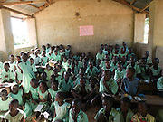 Children at school. This school has 800 children, with more than 100 children per classroom about half the children are sitting on the floor. Many children don't have enough food to eat and so find it difficult to concentrate. Send a Cow is helping families to grow more food to enable them to feed their children and also sell food to pay for school fees.