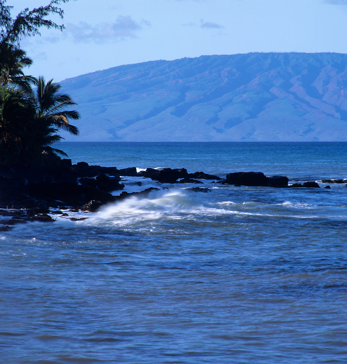 Bright daylight view of Kahana, Maui coastline with Molokai island in distance