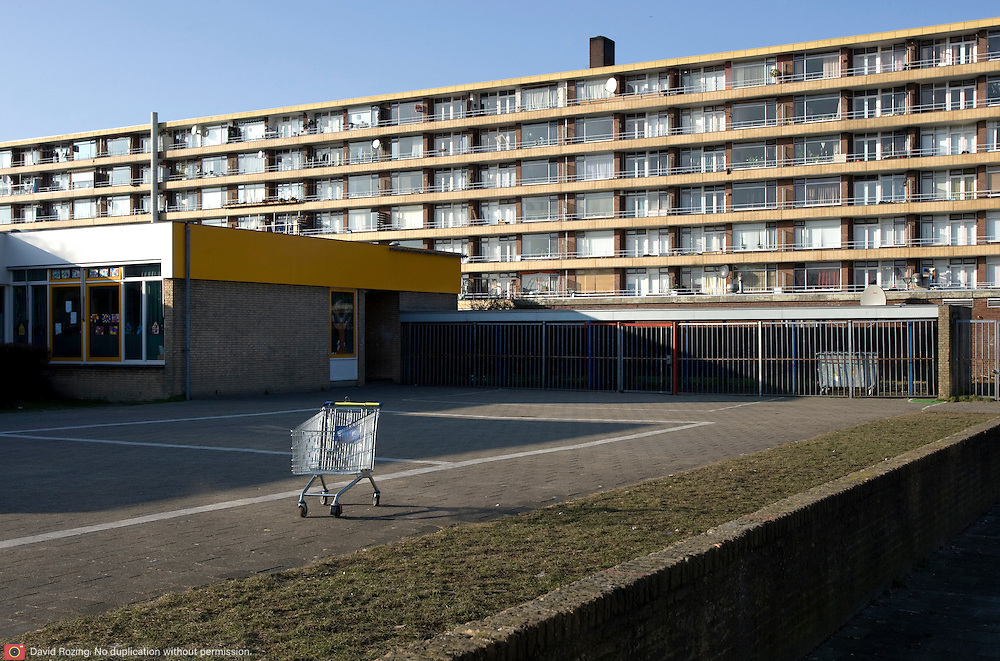 "Nederland Utrecht 31 januari 2009 20090131 Foto: David Rozing ..Serie vogelaarwijk Kanaleneiland .Reportage documentary on deprived area / projects "" Kanaleneiland "" This area is on a list with projects which need help of the government because of degradation in the area etc..Leeg winkelwagentje achtergelaten op schoolplein, op de achtergrond flat .Empty shopping cart left behind on school square, in the background appartments,  antisocial  stilleven, still, stillshot, still life.project, suburb, suburbian, problem. Neighboorhood, neighboorhoods, district, city, problems, multicultural, daily lifeFoto: David Rozing/"
