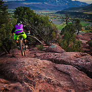 Sam Stevens rolls downhill through the pinyon pines near Carbondale Colorado.