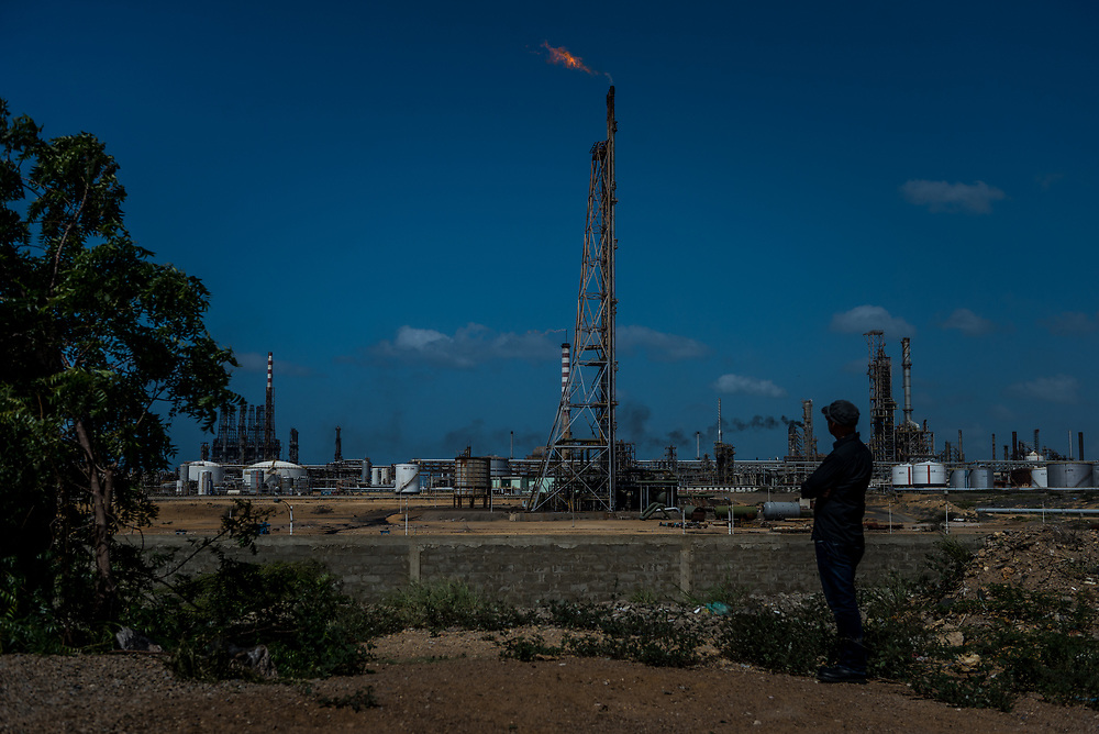 "PARAGUANÁ PENINSULA, VENEZUELA - DECEMBER 7, 2017: A PDVSA worker poses for a portrait near Cardón refinery. The refineries, like most of the company's facilities around the country, have fallen into grave disrepair, forcing severe cutbacks in operations and leading to layoffs and an increase in accidents and injuries, workers and union leaders said. Their deterioration were reflected in several major mishaps in recent weeks. This month, a fire broke out here, leaving only one of five of its distillation units functioning. Workers reported that the emergency crew that responded could do little more than to watch the fire burn out on its own: They had run out of firefighting foam. The disintegration of the refineries has left many workers dispirited. ""Workers have lost all interest,"" said Emilio, a worker in the Cardón refinery who asked that his last name be withheld because he feared punishment by the authorities for criticizing the company. ""They are simply clocking in and clocking out.""  PHOTO: Meridith Kohut for The New York Times"