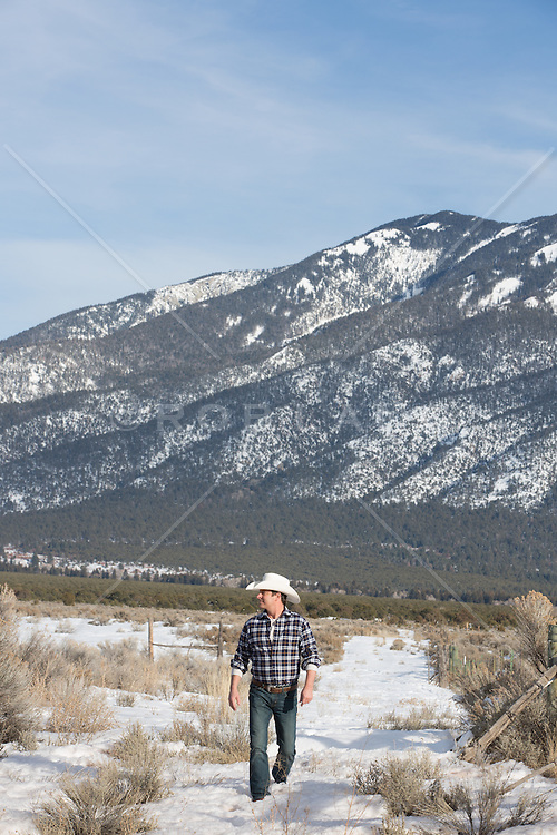 cowboy walking down a snowy path overlooking mountains