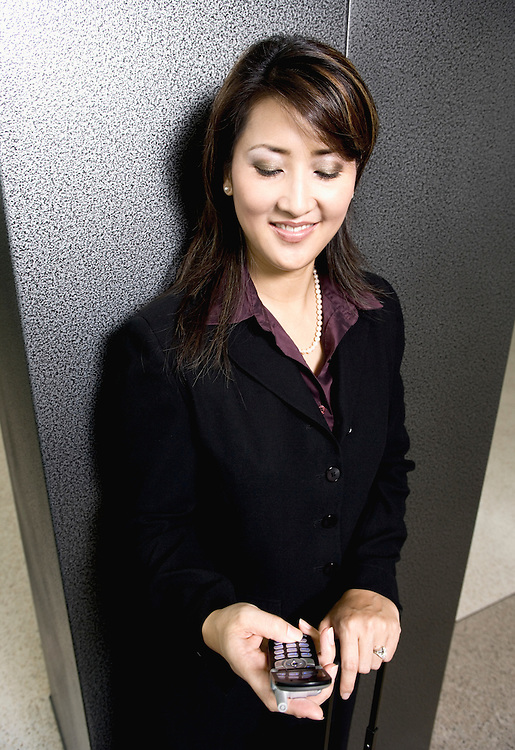 Businesswoman text messaging with mobile phone&amp;#xA;<br />