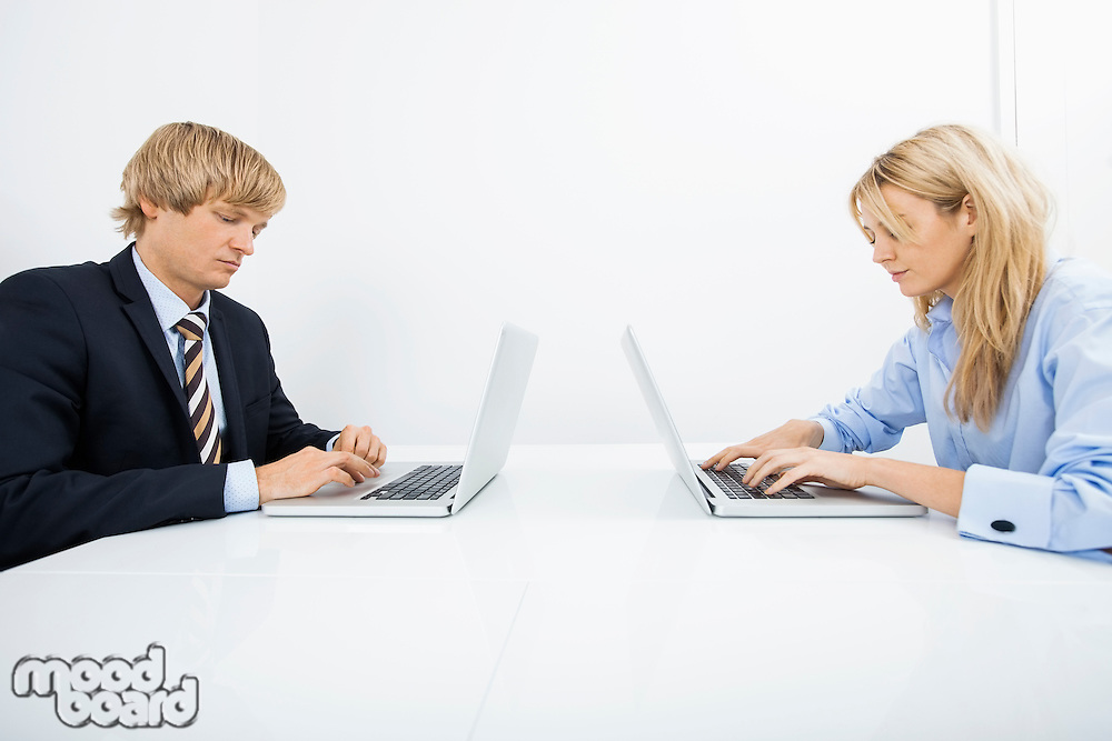 Businesspeople using laptops at desk in office