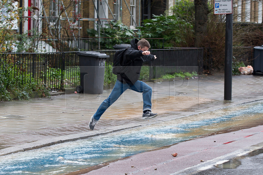 © Licensed to London News Pictures. 28/02/2014. London, UK. A commuter leaps over water being pumped from the site of a burst watermain in Kennington London today (28/02/2014). The watermain, which burst yesterday evening flooding a section of Clapham Road - a major in and out of the city - with thousands of litres of water, has today caused widespread disruption to traffic. Photo credit: Matt Cetti-Roberts/LNP