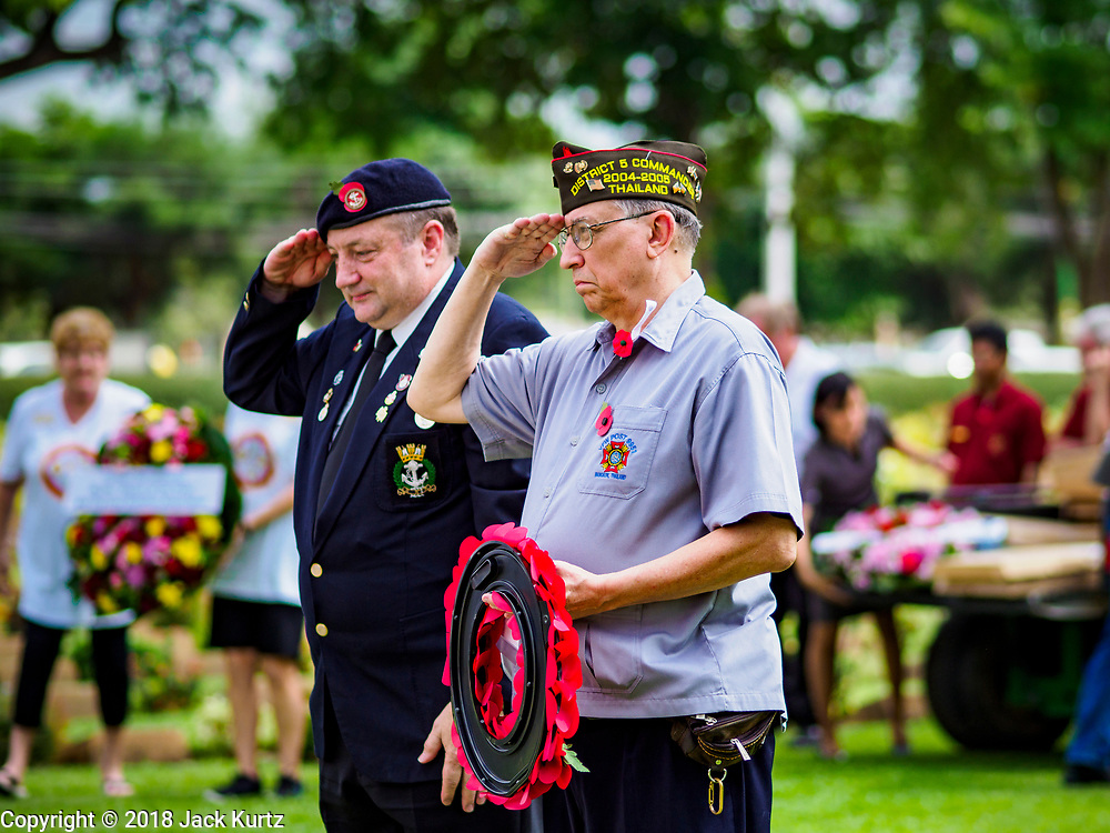 """11 NOVEMBER 2018 - KANCHANABURI, KANCHANABURI, THAILAND:  JERRY KARWACKI, (right) from the Veterans of Foreign Wars post in Bangkok, Thailand, salutes with a veteran of the British Commonweath during the wreath laying at the Rememberance Day ceremony at the Kanchanaburi War Cemetery in Kanchanaburi, Thailand. Kanchanaburi is the location of the infamous """"Bridge On the River Kwai"""" and was known for the """"Death Railway"""" built by Japan during World War II using allied, principally British, Australian and Dutch, prisoners of war as slave labor. There are 6,982 people buried in the cemetery, including 5,000 Commonwealth soldiers and 1,800 Dutch soldiers. November 11, 2018 marked the 100th anniversary of the end of World War I, celebrated as Rememberance Day in the UK and the Commonwealth and Veterans' Day in the US.   PHOTO BY JACK KURTZ"""