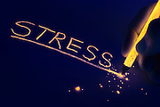 "A glowing pencil tip shatters after underlining the word ""stress"".Black light"