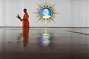 15 February 2010 - Pathum Thani, Thailand - A mink walks past an image of the founder of the Dhammakaya Temple. Photo credit: Luke Duggleby