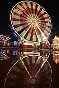 Big wheel ride reflected in standing water at dusk, Hull fair, Kingston upon Hull, East Yorkshire, UK.