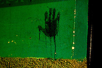 A blody hand print stains the wall near a scene where relatives mourn the deaths of two family members killed in a drive by shooting at a wake in Zone 6 Guatemala city  Monday Oct. 29, 2007 in Guatemala. Witnneses say the gang related violence stemmed from the murder the night before just a few blocks away.                                                                 ..........