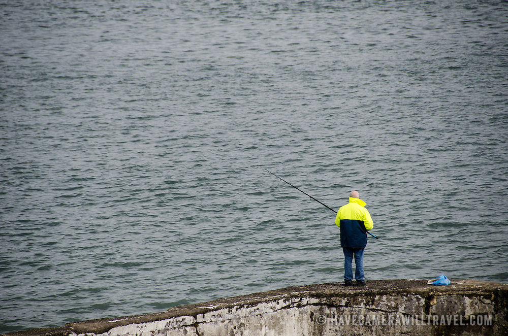A solitary fisherman casts a line in Beaumaris on the island of Anglesey of the north coast of Wales, UK.