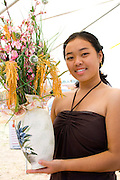 Beautiful Hmong woman holds bouquet of flowers in vase. Hmong Sports Festival McMurray Field St Paul Minnesota USA