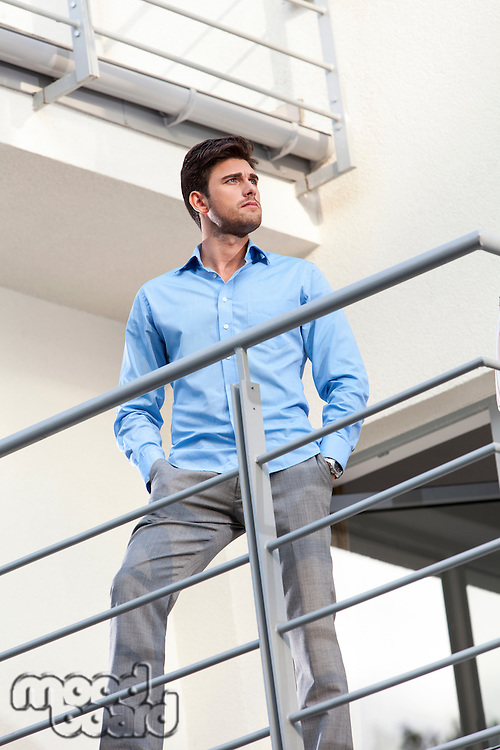 Thoughtful young businessman with hands in pockets standing at hotel balcony