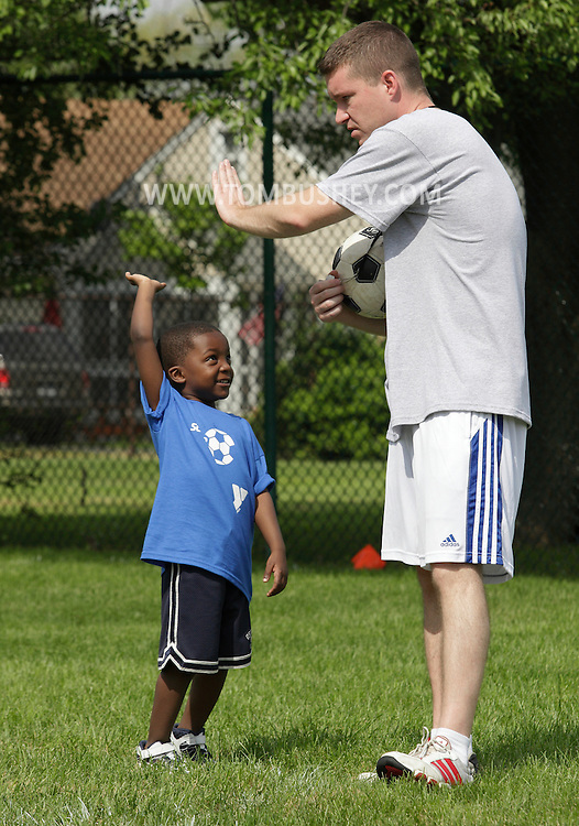 Middletown, New York - A boy gets ready to high-five a coach during a soccer program at the Middletown YMCA on May 28, 2011.