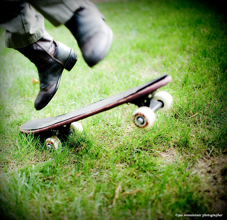 A boy wearing cowboy boots jumps off of his skateboard.
