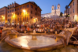 Europe, Italy, Rome, Barcaccia  Fountain and crowd of people on Spanish Steps at dusk, with  Trinità dei Monti church on top