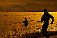 Silhouette of people dipnetting at the mouth of the Kenai River as it spills out into Cook Inlet in Southcentral Alaska during Summer.