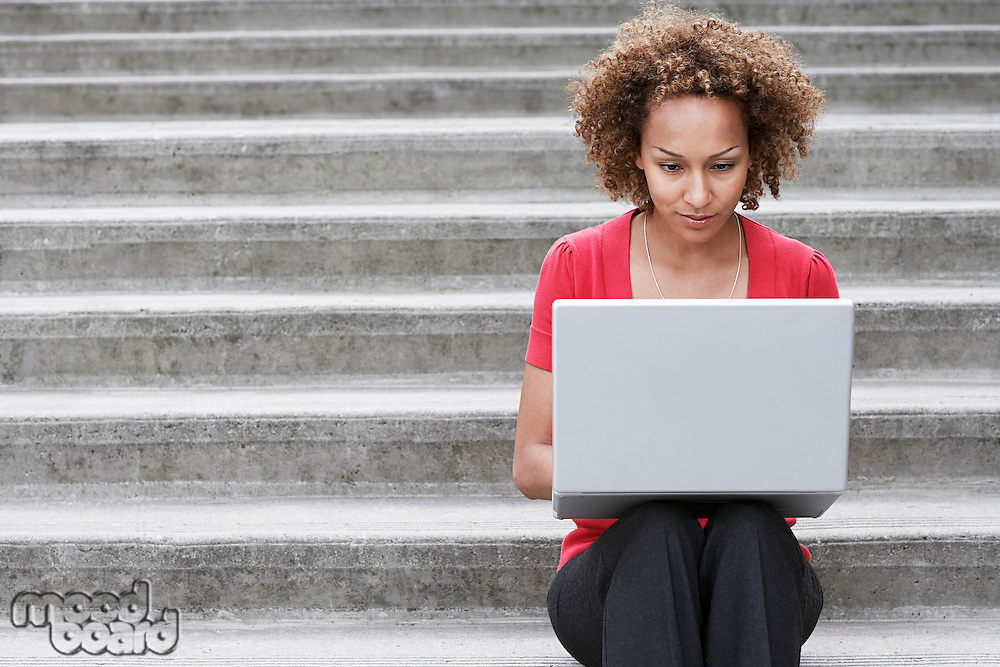 Woman using laptop on steps