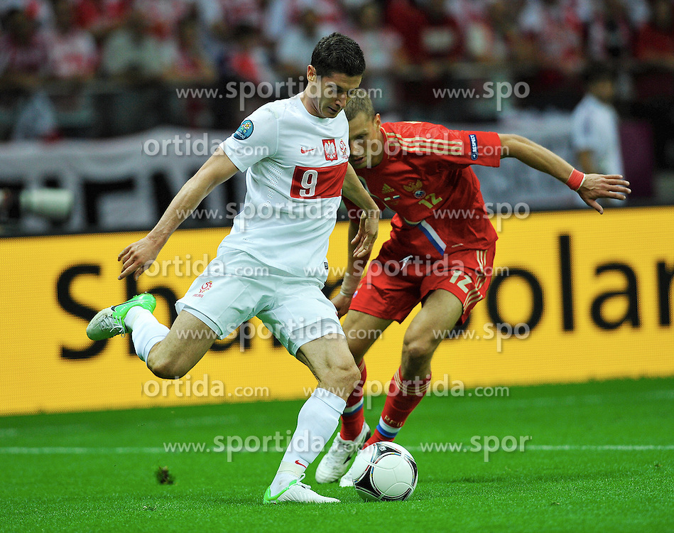 Warsaw 12/06/2012.POLAND, WARSAW .Poland's Robert Lewandowski fights for the ball with Aleksei Berezutski of Russia during the Euro 2012 football championships match Poland vs. Russia, on June 12, 2012 at the National Stadium in Warsaw. .Photo by: Piotr Hawalej / WROFOTO