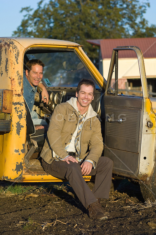 Two guys hanging out of an old yellow pickup truck