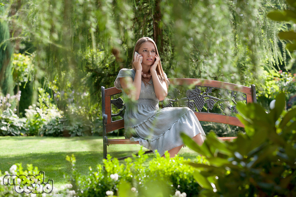 Tensed young woman using cell phone on bench in park