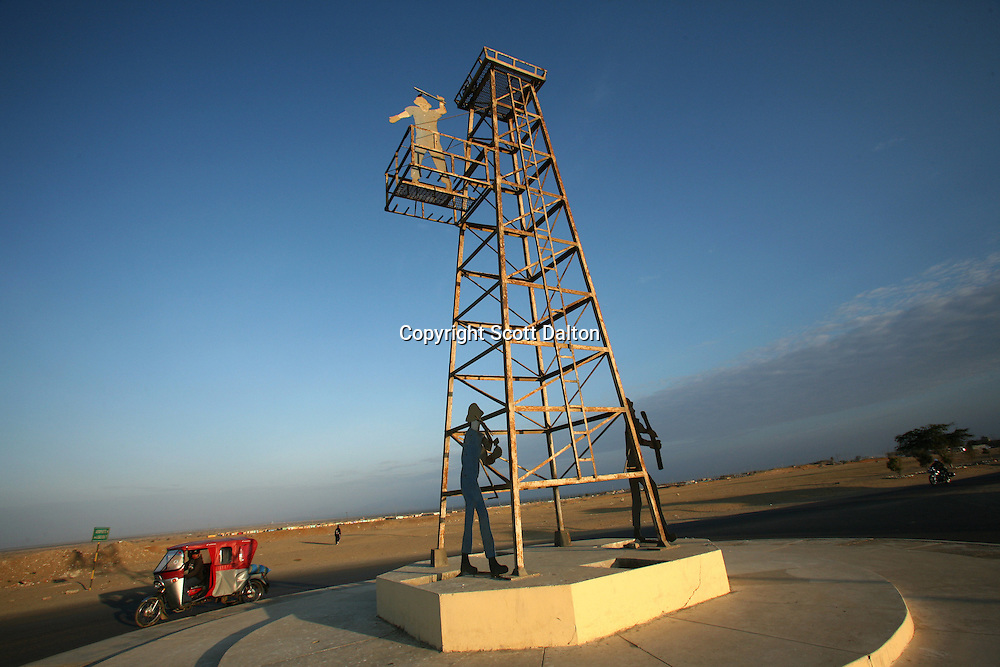 A motorbike taxi goes by a roundabout with a monument to the oil industry in Talara on November 9, 2007. Talara, located on Peru's northern coast, is Peru's main oil producing region and the Chinese company SAPET has an oil field in the region. (Photo/Scott Dalton)