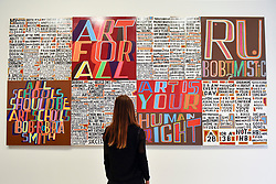 """© Licensed to London News Pictures. 04/09/2018. LONDON, UK.  A staff member views """"The Secret of a Good Life"""", by celebrated artist Bob and Roberta Smith RA, the first display by a Royal Academician in the new Ronald and Rita McAulay Gallery, a new space dedicated to site-specific installations by Royal Academicians in the new Royal Academy in Piccadilly.  This and other works are on display 4 September to 3 February 2019.  Photo credit: Stephen Chung/LNP"""
