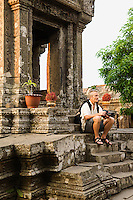 Photographer Sitting on Steps of Ancient Building
