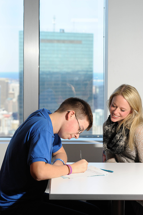 A Citizens School student works with his lawyer writing mentor at Ropes and Gray Law Firm.