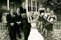 classic shot of wedding party in front of a traditional antique building with stone and glass windows. attractive happy couple just got married with best friends