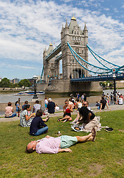 © Licensed to London News Pictures. 05/07/2019. London, UK.  Office workers and tourists enjoy the warm and sunny weather near Tower Bridge in London on Friday lunchtime. The UK continues to enjoy seasonally warm weather this week, but rain is forecast across the country during the next few days. Photo credit: Vickie Flores/LNP
