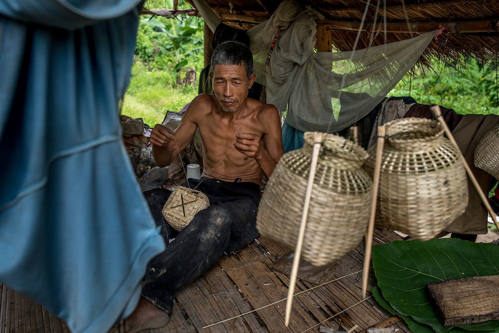 A man stiches small fishing traps together in the village of Khoc Kham. The village is not connected to the main electrical grid and many residents operate their own turbines to power lights and sometimes small appliances.
