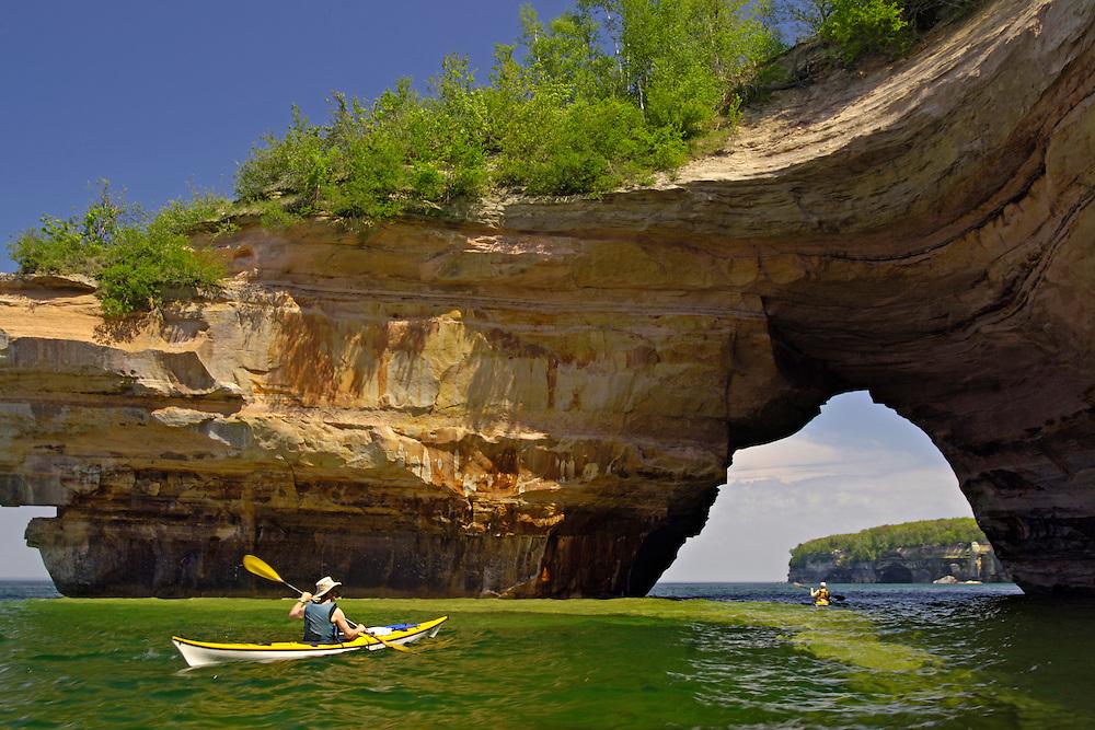 Sea kayakers at the Lovers Leap rock arch on Lake Superior at Pictured Rocks National Lakeshore near Munising Michigan Upper Peninsula.