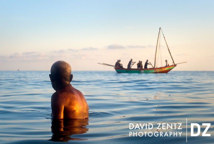 A pilgrim watches a passing boat as he bathes in the sea during a sunrise voodou ritual at Bord de Mer de Limonade, on the north coast of Haiti on July 25, 2008. After renewing their faith in the mud pit at Plaine du Nord on the days prior, pilgrims migrate to the nearby water, their faith renewed. The site is also where Christopher Columbus' Santa Maria sank in 1492.