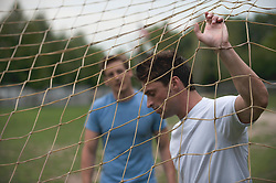 two men behind a soccer net about to have a conversation