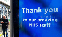 © Licensed to London News Pictures. 27/03/2020. London, UK. A man walks past a 'Thank you to our amazing NHS staff' digital display at a bus stop in north London, showing appreciation to the NHS staff. Photo credit: Dinendra Haria/LNP