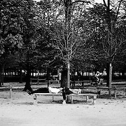 Individuals sleep on stone seating in the tranquil setting of the Jardin des Tuileries on in Paris, France. October 23, 2007. Photo Tim Clayton..Paris is often known as 'The City of Love' but like any major City in the world, the inhabitants often live a singular existence, going about their daily lives in relative solitude. Parisians are respectful of each others space, often courteous and polite while extremely conscious of their own image. While love can be seen openly around the streets of Paris, so can the separate lives of Parisians.