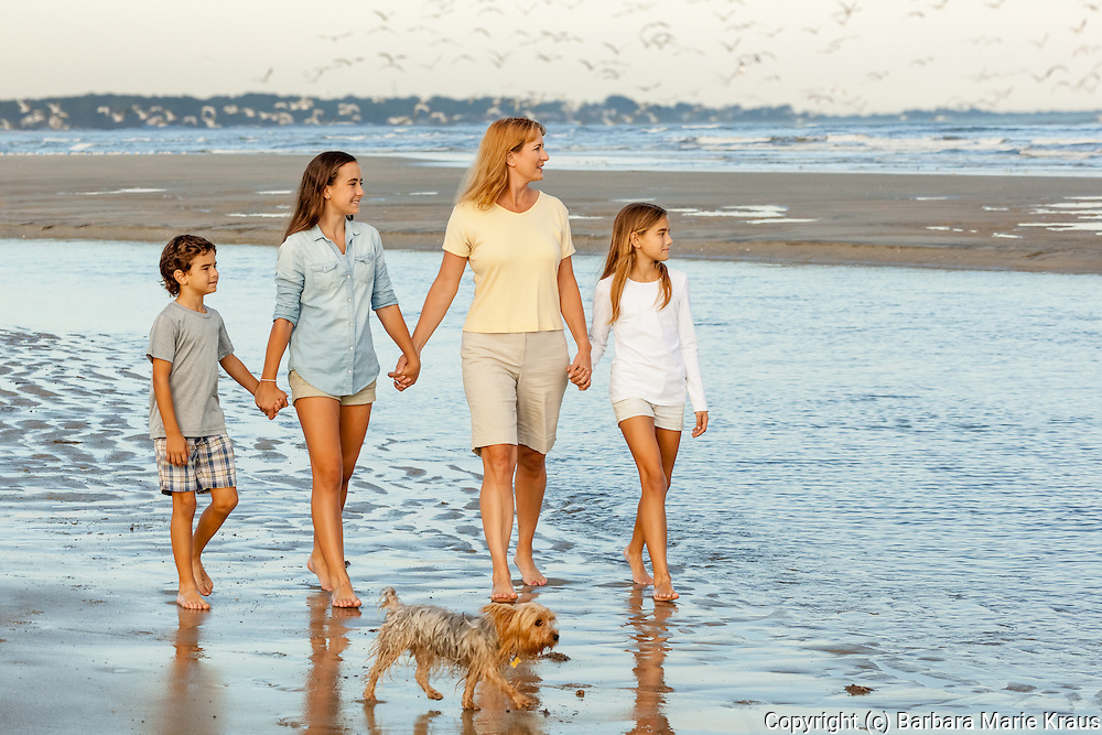 A mother walks with her three children in the surf. The family dog walks too.