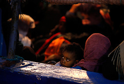 An African child immigrant fleeing the unrest in Libya waits to disembark from their boat at the Armed Forces of Malta Maritime Squadron base in Valletta's Maramxett Harbour March 28, 2011. More than 500 Eritreans and Somalis thought to be fleeing the violence in Libya - including tens of women and children - arrived in two large wooden boats Monday evening after a three-day journey at sea. Around half the people arriving on the first boat wanted to continue on their journey towards Italy but the others asked to be brought to shore for medical treatment, according to local media. <br /> REUTERS/Darrin Zammit Lupi (MALTA - Tags: POLITICS CIVIL UNREST SOCIETY) MALTA OUT. NO COMMERCIAL OR EDITORIAL SALES IN MALTA - RTR2KJ3F