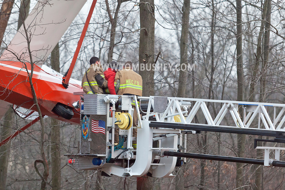 Town of Wallkill, New York - Two Mechanicstown firefighters work to remove the pilot of a glider that crashed into trees at Randall Airport on Dec. 2, 2012.